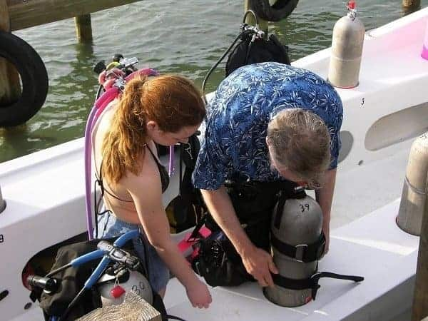 Scuba divers helping eachothers gearing up